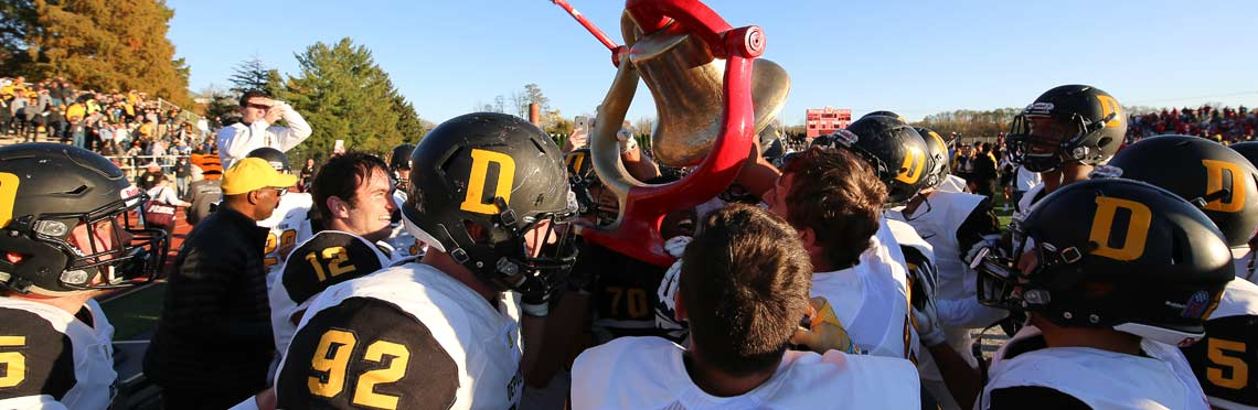 Football players hoist the Monon Bell following a win