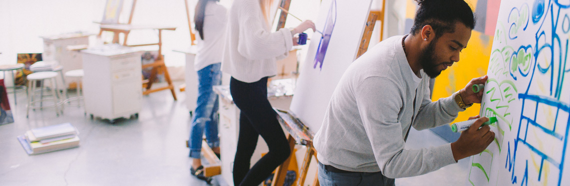 Students painting on canvas in an art class